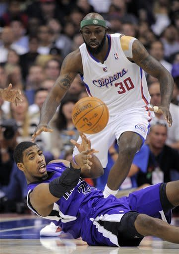 Sacramento Kings center Jason Thompson, bottom, passes the ball from the floor as Los Angeles Clippers forward Reggie Evans watches during the first half of their NBA basketball game, Saturday, April 7, 2012, in Los Angeles. (AP Photo/Mark J. Terrill)