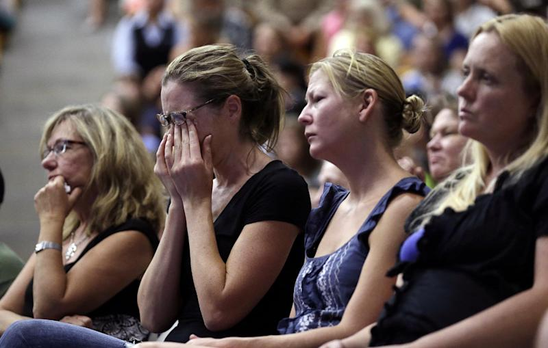 Mourners seated in a section reserved for friends and family react during a memorial service Monday, July 1, 2013, in Prescott, Ariz., honoring the 19 firefighters killed battling a wildfire near Yarnell, Ariz., Sunday. The elite crew of firefighters was overtaken by the out-of-control blaze as they tried to protect themselves from the flames under fire-resistant shields. (AP Photo/Chris Carlson)