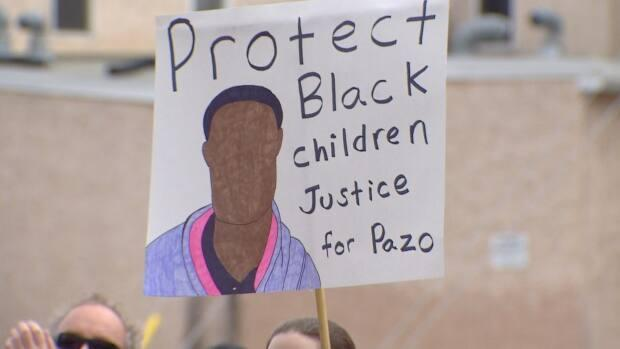 A sign at Saturday's rally calls for justice for Pazo, after his family says police mishandled the aftermath of a schoolyard attack that sent him to hospital.