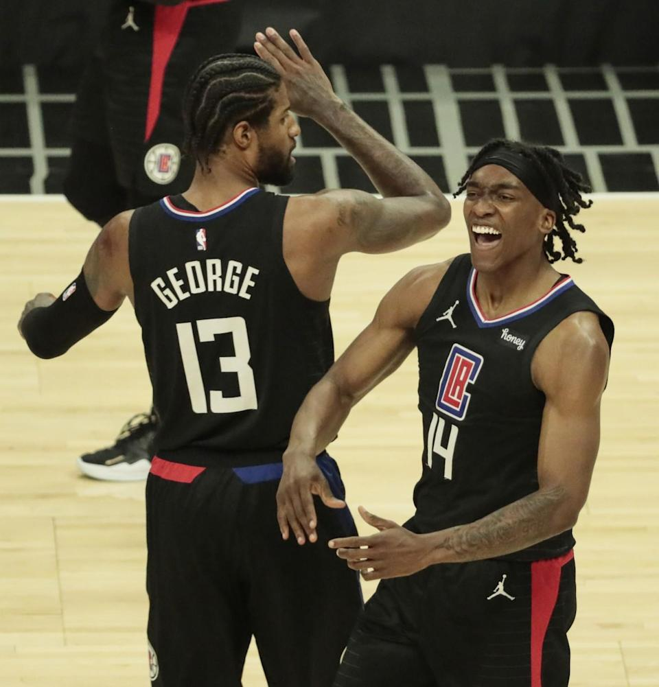 Clippers guard Terance Mann #14 celebrates with teammate Paul George after getting fouled while making a layup.