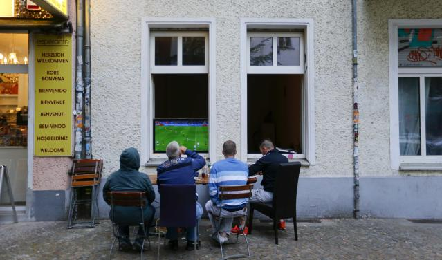 Soccer Football - World Cup - Group F - Germany vs Sweden - Berlin, Germany - June 23, 2018 Soccer fans watch the match from outside of a flat. REUTERS/Hannibal Hanschke