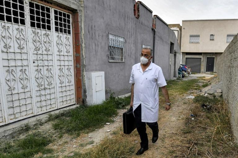 Tunisian physician Hichem Ouadi walks along a street in the Tunisian town of Bou Mhel during a house visit to a patient suffering from Covid-19