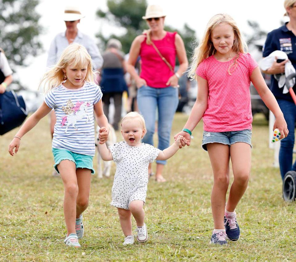 <p>Savannah and Isla Phillips run ahead of their Aunt Zara, while holding hands with their cousin, Lena Tindall, at a British festival in Gatcombe Park. </p>