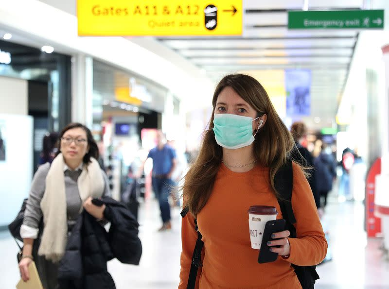 A woman wears a surgical mask as she walks through Terminal 5 at Heathrow Airport in London