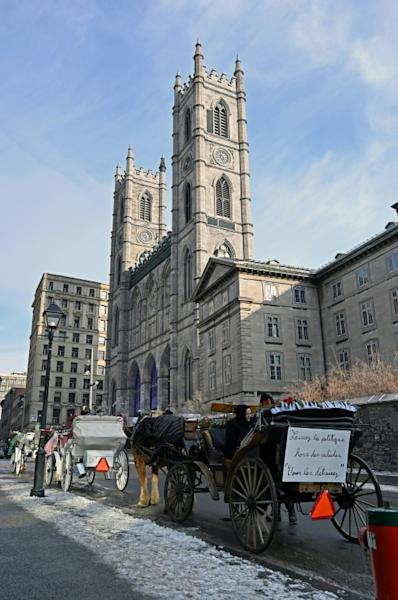 Horse-drawn carriages line up in front of the Notre-Dame basilica in Old-Montreal, waiting for tourists in Montreal, Quebec, Canada on December 22, 2019.Montreal's horse-drawn carriages will be taken off the roads on December 31, ending a long feud between the city and coachmen and a quaint means of local travel that dates back to the 1600s. (AFP Photo/Eric THOMAS)