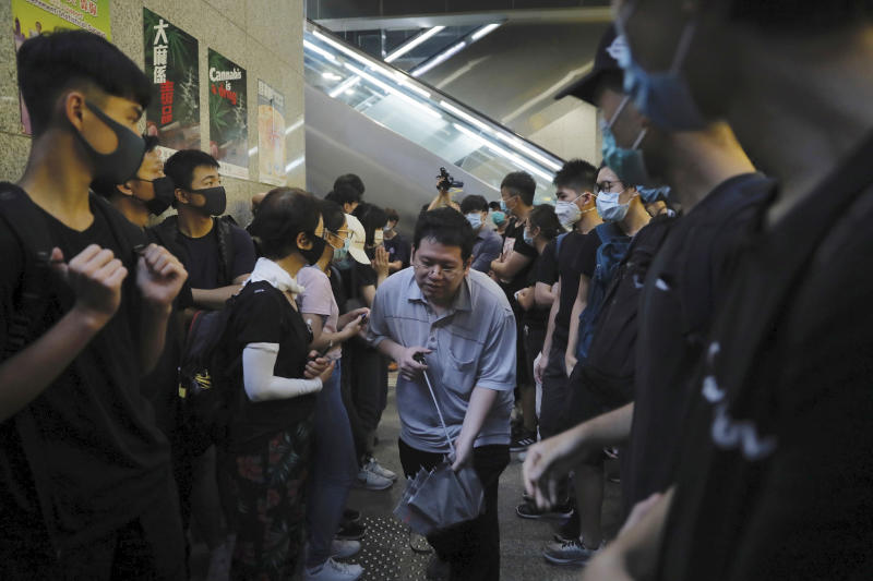 A man squeezes through protesters blocking the lobby of the Hong Kong Revenue Tower in Hong Kong on Monday, June 24, 2019. Hong Kong has been rocked by major protests for the past two weeks over legislative proposals that many view as eroding the territory's judicial independence and, more broadly, as a sign of Chinese government efforts to chip away at the city's freedoms. (AP Photo/Kin Cheung)