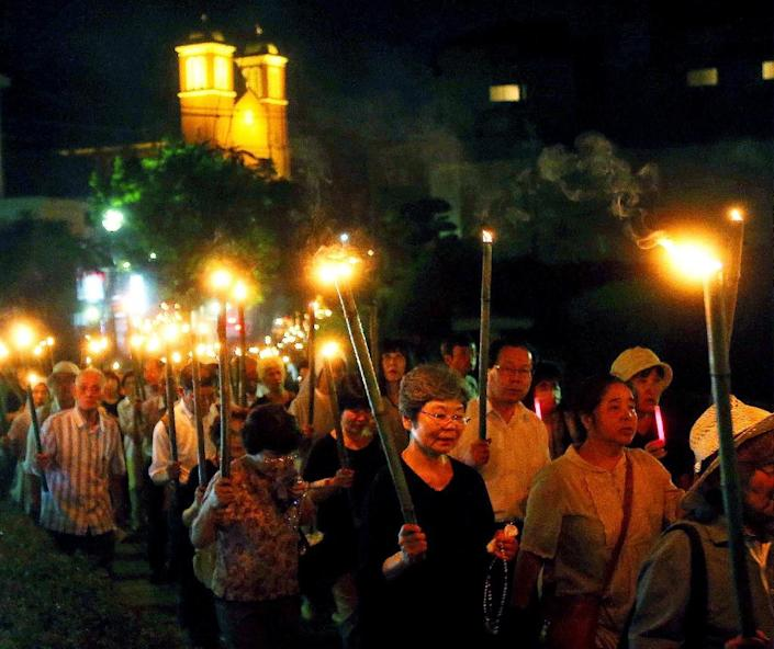 Nuns and Catholics hold bamboo torches during a peace march on the southern island of Kyushu on August 9, 2015, marking the 70th anniversary of the atomic bombing of Nagasaki that claimed more than 74,000 lives almost instantly (AFP Photo/JIJI PRESS)