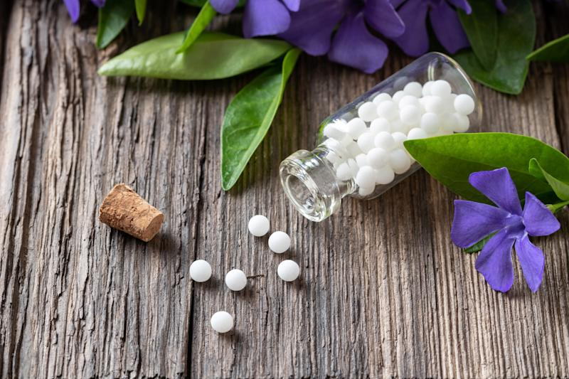 A bottle of homeopathic pills with fresh vinca minor