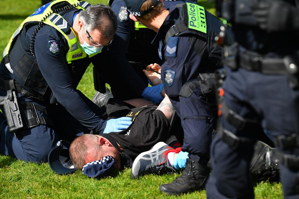 A protester is arrested by Victorian Police Officers outside of the Shrine of Remembrance in Melbourne on Saturday. Source: AAP