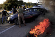 A Lebanese soldier asks a driver to move away from burning tires that were set on fire by protesters to block a highway that leads to Beirut's international airport, in Beirut, Lebanon, Tuesday, March 2, 2021. Scattered protests broke out in different parts of Lebanon Tuesday after the Lebanese pound hit a record low against the dollar on the black market, a sign of the country's multiple crises deepening with no prospects for a new Cabinet in the near future. (AP Photo/Hussein Malla)