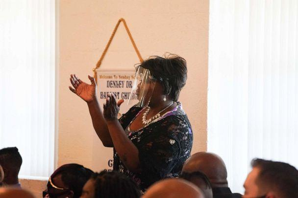PHOTO: A family member wearing a face shield sings during a double funeral service for Lola M. Simmons-Jones and her daughter Lashaye Antoinette Allen, who both died of coronavirus, at the Denley Drive Missionary Baptist Church in Dallas on July 30, 2020. (Bryan R. Smith/AFP via Getty Images)