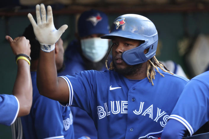 Toronto Blue Jays' Vladimir Guerrero Jr. is congratulated by teammates after scoring on a single by Randal Grichuk against the Oakland Athletics during the first inning of a baseball game in Oakland, Calif., Wednesday, May 5, 2021. (AP Photo/Jed Jacobsohn)