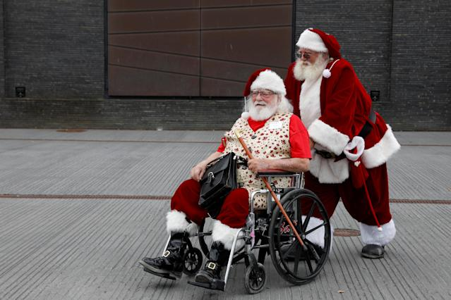 <p>A man helps another man in a wheelchair as they are dressed as Santa Claus during the World Santa Claus Congress, an annual event held every summer in Copenhagen, Denmark, July 23, 2018. (Photo: Andrew Kelly/Reuters) </p>