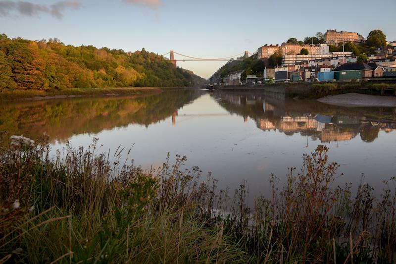 Sun rises over the Avon Gorge as the Clifton Suspension Bridge and Autumnal trees are reflected in the River Avon, Bristol.