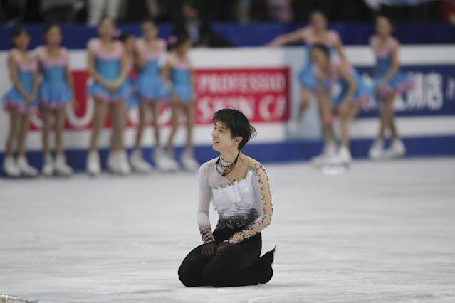 Yuzuru Hanyu of Japan sits on the ice after his performance during the men's free skating in the World Figure Skating Championships in Saitama, near Tokyo, Friday, March 28, 2014. Hanyu barely topped the free skate to become the first man in 12 years on Friday to win the Olympic and world figure skating titles in the same year. (AP Photo/Koji Sasahara)