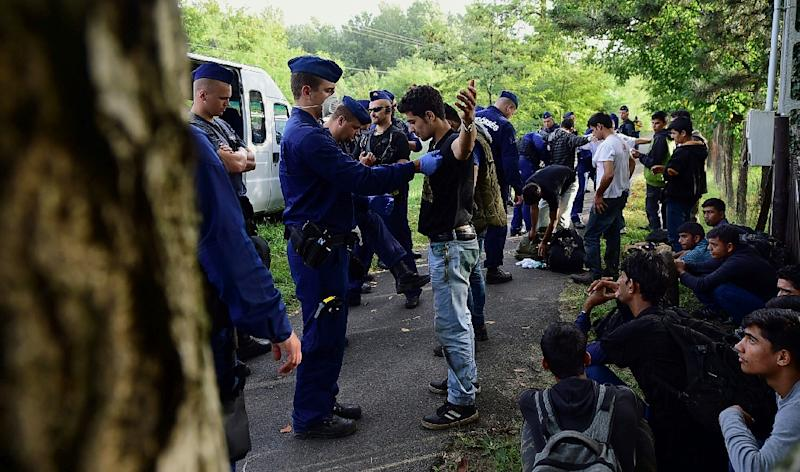 Migrants being arrested by Hungarian police near the village of Asotthalom on September 17, 2015 (AFP Photo/Attila Kisbenedek)