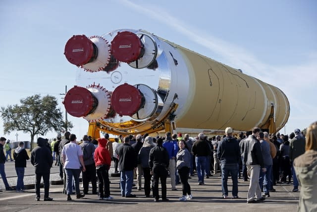 Employees and contractors watch as the core stage of Nasa's Space Launch System rocket, that will be used for the Artemis 1 Mission, is moved to the Pegasus barge, at the Nasa Michoud Assembly Facility where it was built, in New Orleans