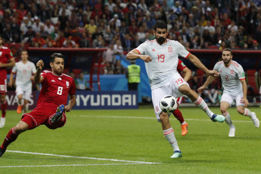 Spain's Diego Costa, right, tries to shot as Iran's Morteza Pouraliganji tries to block during the group B match between Iran and Spain at the 2018 soccer World Cup in the Kazan Arena in Kazan, Russia, Wednesday, June 20, 2018. (AP Photo/Frank Augstein)