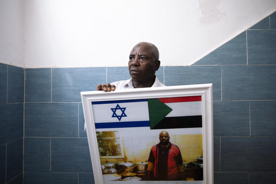 Sudanese migrant Attom Alialdom 56, poses for a photo as he holds a photo of his old restaurant decorated with Sudanese and Israeli flags, outside his house in south Tel Aviv, Israel, Sunday, Oct. 25, 2020. After Israel and Sudan agreed this month to normalize ties, some 6,000 Sudanese migrants in Israel are again fearing for their fate. Israel has long grappled with how to deal with its tens of thousands of African migrants. (AP Photo/Oded Balilty)