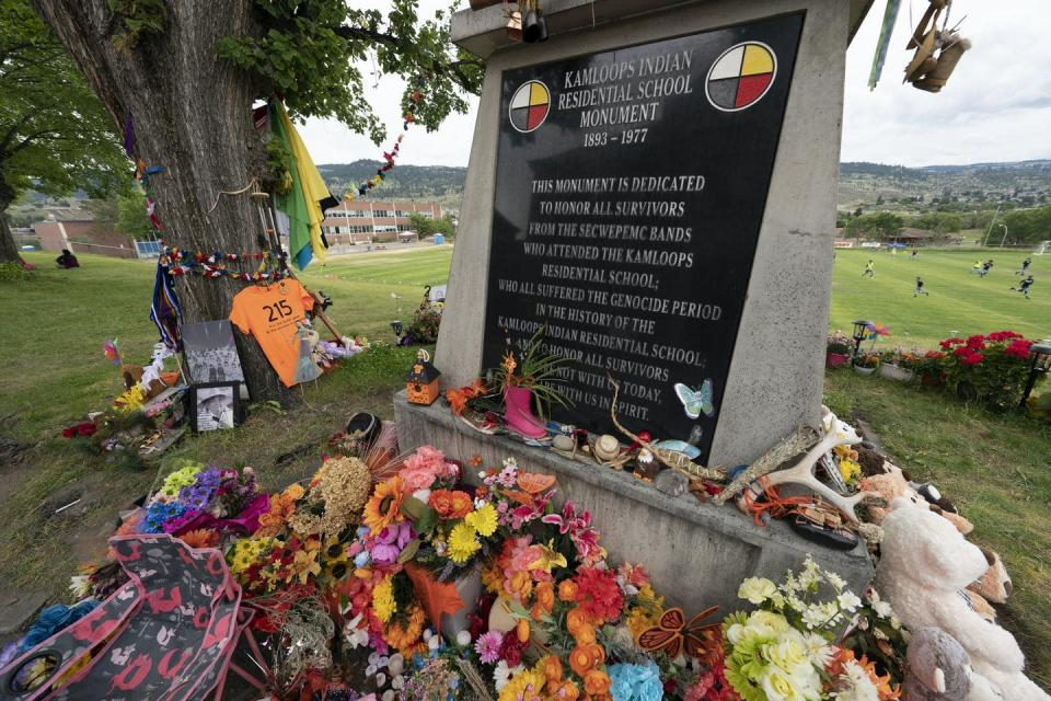 A memorial is covered in toys, orange, flowers to commemorate those who died at IRS
