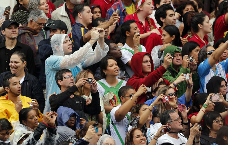 Pilgrims take pictures as they wait for Pope Francis to leave the Municipal Theater where he gave a conference as part of World Youth Day events in Rio de Janeiro, Brazil, Saturday, July 27, 2013. (AP Photo/Jorge Saenz)