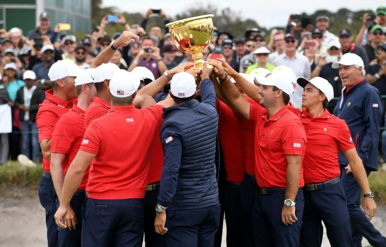 US team captain Tiger Woods (C, back to camera) and teammates celebrate with the trophy after winning the Presidents Cup golf tournament (AFP Photo/WILLIAM WEST)