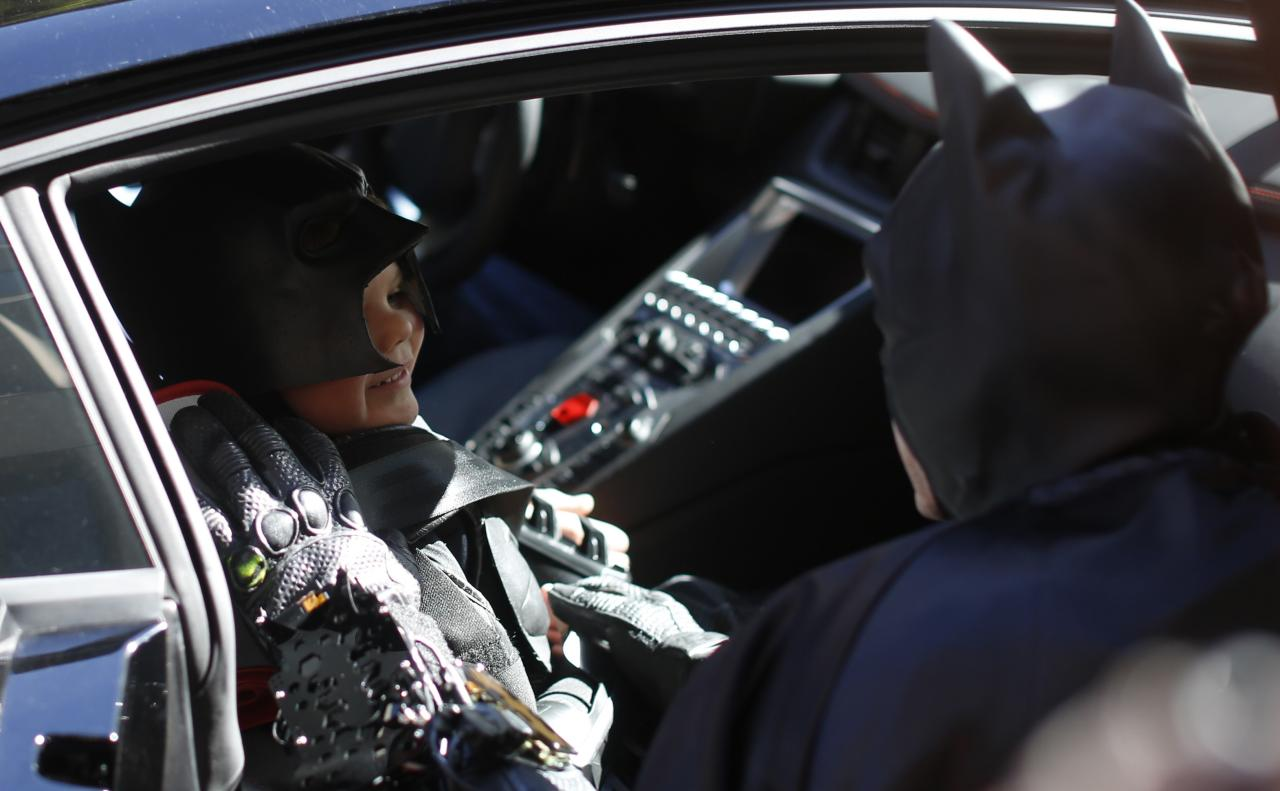 """Five-year-old leukemia survivor Miles dressed as """"Batkid"""" speaks to a man dressed as Batman from the Batmobile as part of a day arranged by the Make-A-Wish Foundation in San Francisco, California November 15, 2013. The young cancer survivor will be treated to various super hero scenarios including receiving a commendation at San Francisco City Hall. REUTERS/Stephen Lam (UNITED STATES - Tags: SOCIETY)"""