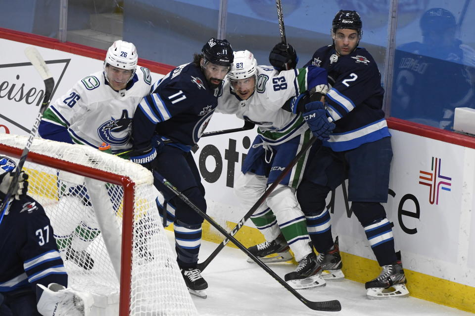 Winnipeg Jets' Nate Thompson (11) and Dylan DeMelo (2) and Vancouver Canucks' Antoine Roussel (26) and Jay Beagle (83) battle for the puck behind the Jets net during first period NHL hockey action in Winnipeg, Manitoba on Tuesday March 1, 2021. (Fred Greenslade/The Canadian Press via AP)
