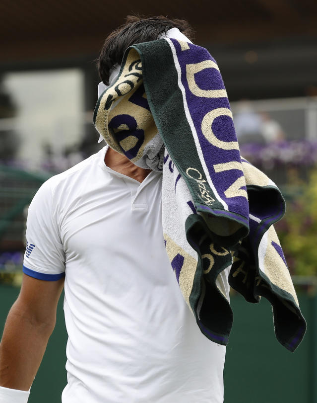 Italy's Fabio Fognini wipes his face as he plays United States' Tennys Sandgren in a Men's singles match during day six of the Wimbledon Tennis Championships in London, Saturday, July 6, 2019. (AP Photo/Alastair Grant)
