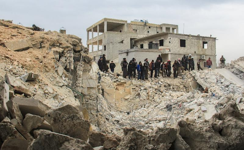 People stand by as Syrian civil defence volunteers, known as the White Helmets, dig through the rubble of a mosque following a reported airstrike in the village of Al-Jineh in Aleppo province on March 17, 2017