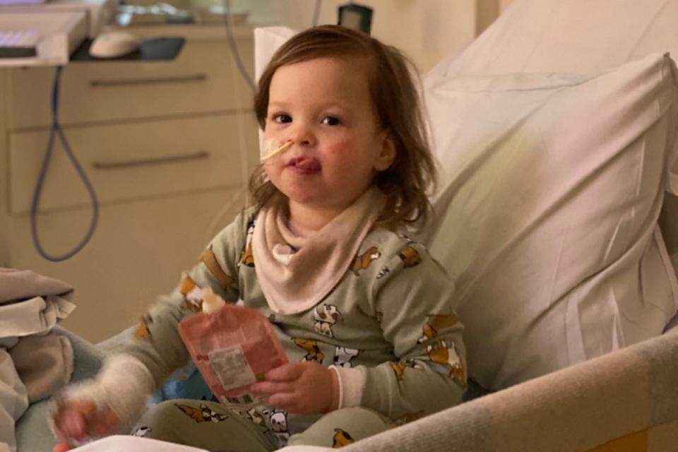 Chloé is pictured sitting in her hospital bed with a tube in her nose. Source: supplied