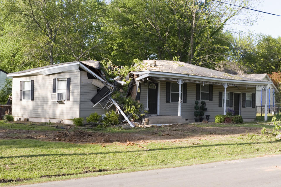 A damaged home after a large tree fell on it during a tornado. (Photo: Getty Images)