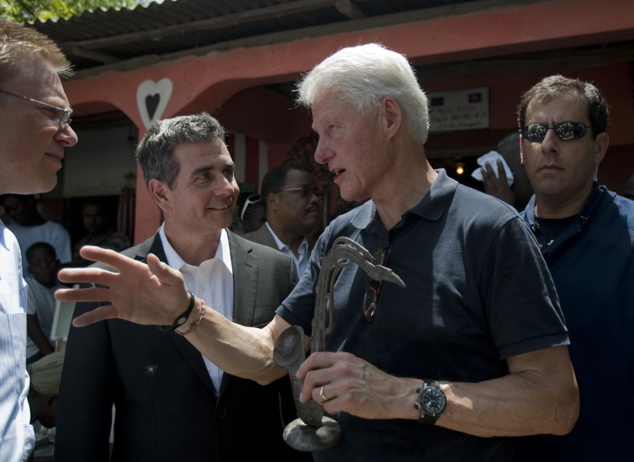 Former U.S. President and UN special envoy to Haiti, Bill Clinton, center, carrying a piece of art, a present from artisans depicting a saxophone, talks to Scott Griffin, second from left, Vice President of GREIF Company, during a visit to an artisan center in Croix des Bouquets, outskirts of Port-au-Prince, Haiti, Tuesday, Aug. 16, 2011. (AP Photo/Dieu Nalio Chery)