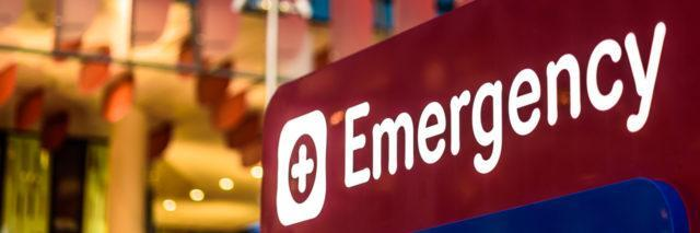 """An """"Emergency"""" Sign in front of a hospital in the early evening"""