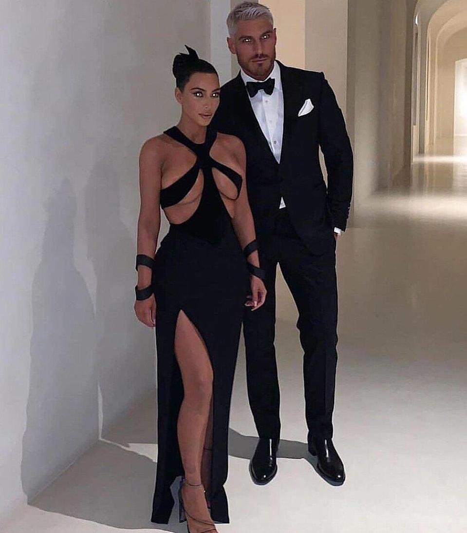"""Kim posed in a <a href=""""https://people.com/style/kim-kardashian-wears-sexiest-dress-ever/"""" rel=""""nofollow noopener"""" target=""""_blank"""" data-ylk=""""slk:bust-baring black dress"""" class=""""link rapid-noclick-resp"""">bust-baring black dress</a> with her hair stylist Chris Appleton on the night he won a Hollywood Beauty Award in the same portrait-worthy white hallway. Appleton posted the same photo captioned, """"Prom night."""""""