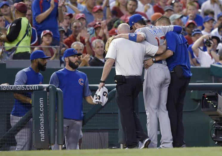 Chicago Cubs third baseman Kris Bryant is helped off the field after rolling his right ankle on the third base bag. (AP)