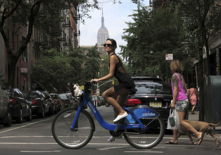 FILE PHOTO: The Empire State Building is seen in the distance as a woman rides a Citibike in the Soho neighbourhood of New York