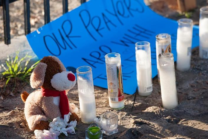 A stuffed animal, candles and a sign are part of a makeshift memorial near the Inland Regional Center on December 5, 2015, in San Bernardino, California (AFP Photo/Greg Vojtko)
