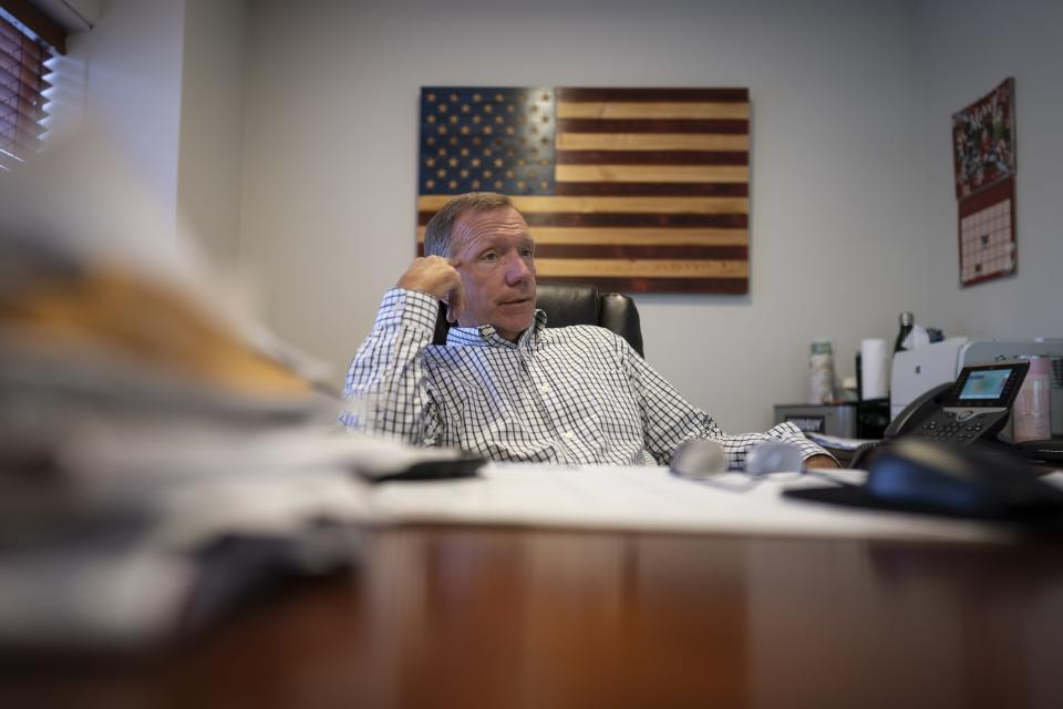 """Retired NYPD Officer Ken Winkler, sits in his office on Tuesday, Aug. 3, 2021, in New York. Winkler helped coordinate the New York Police Department Emergency Service Unit response on-scene at the World Trade Center on Sept. 11, ducking behind a truck to escape the debris when the south tower collapsed. """"It went from a clear day to various shades of gray and black … from kind of organized chaos to just chaos,"""" recalls Winkler. (AP Photo/Wong Maye-E)"""