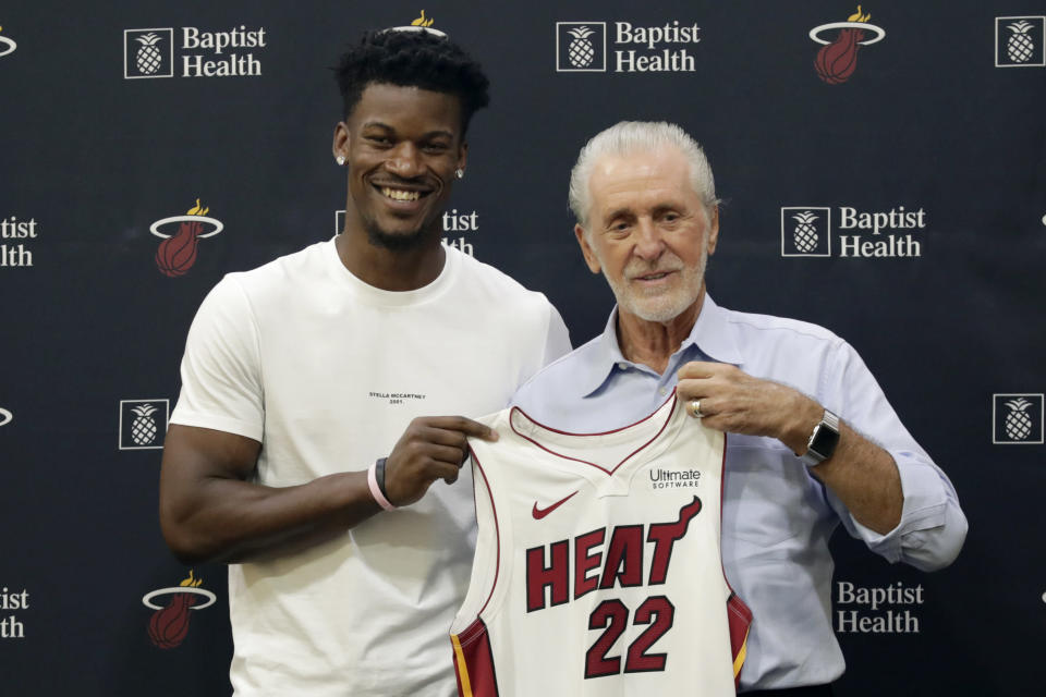 Miami Heat guard Jimmy Butler, left, holds his new jersey as he stands with Miami Heat president Pat Riley, during an NBA basketball news conference, Friday, Sept. 27, 2019, in Miami. Butler spoke publicly for the first time since the July trade that brought him to South Florida as the new face of the franchise. (AP Photo/Lynne Sladky)