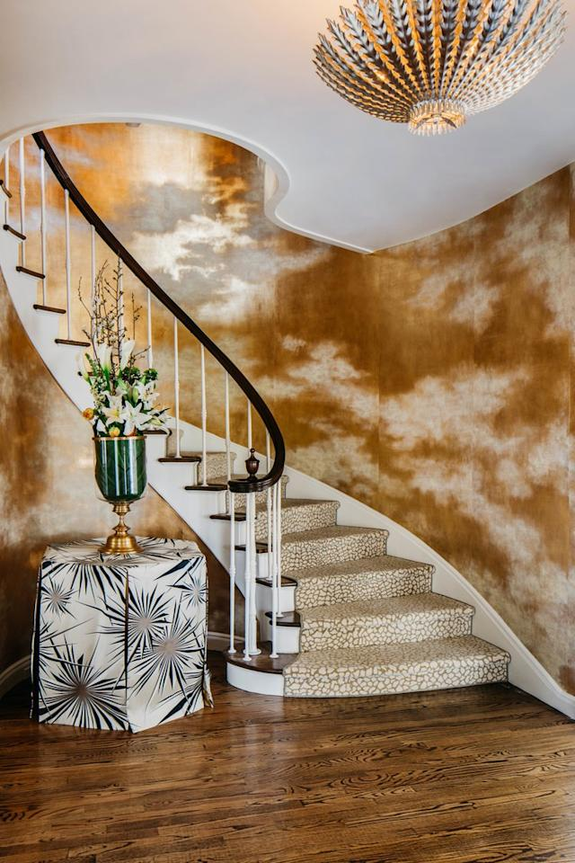 """The entry was """"inspired by the glint of water that can almost be touched,"""" explains Malone. A gilded paper with an amazing cloud effect by de Gournay almost needs no help from the HEWN + Fuse Lighting chandelier to illuminate the spiral staircase."""