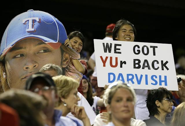 "Texas Rangers' Yu Darvish fans hold up a picture of his likeness with a sign that reads ""We Got YUr Back Darvish"", during a baseball game against the Pittsburgh Pirates, Monday, Sept. 9, 2013, in Arlington, Texas. (AP Photo/Tony Gutierrez)"
