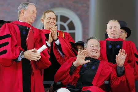 Former U.S. president George H. W. Bush (R) acknowledges the applause as he receives a honorary Doctor of Laws degree during the 363rd Commencement Exercises at Harvard University in Cambridge, Massachusetts May 29, 2014. Also pictured is fellow honorary degree recipient former New York mayor Michael Bloomberg (L). REUTERS/Brian Snyder (UNITED STATES - Tags: EDUCATION POLITICS)