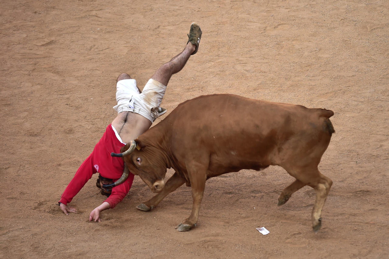 <p>A reveller jumps over a heifer following the running of the bulls at the San Fermin Festival in Pamplona, northern Spain, July 11, 2018. (Photo: Alvaro Barrientos/AP) </p>