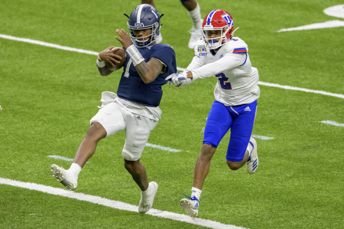 Georgia Southern quarterback Shai Werts (1) scores his second touchdown, the team's third, as Louisiana Tech defensive back Zach Hannibal (2) defends during the first half of the New Orleans Bowl NCAA college football game in New Orleans, Wednesday, Dec. 23, 2020. (AP Photo/Matthew Hinton)