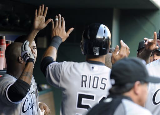 Chicago White Sox's Alex Rios (51) is congratulated by teammates in the dugout after scoring a run in the first inning during a baseball game against the Texas Rangers, Tuesday, April 30, 2013, in Arlington, Texas. (AP Photo/Matt Strasen)