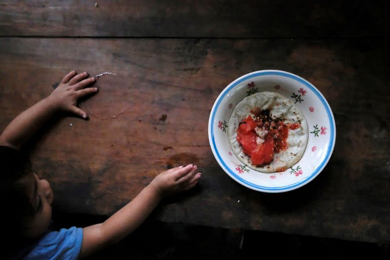 Carlos, a 22-months old boy, reaches for a plate with a tortilla with salt and a cooked tomato, at his home, in La Palmilla