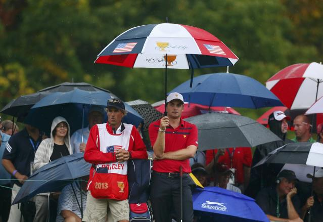 Keegan Bradley of the U.S. stands in the rain on the eighth hole while playing with teammate Phil Mickelson against International team members Ernie Els of South Africa and Brendon de Jonge of Zimbabwe in their four ball match at the 2013 Presidents Cup golf tournament at Muirfield Village Golf Club in Dublin, Ohio October 5, 2013. REUTERS/Chris Keane (UNITED STATES - Tags: SPORT GOLF ENVIRONMENT)