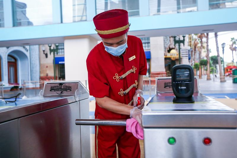 A posed photo of a Universal Studios Singapore employee cleaning an entry gate. Resorts World Singapore attractions on Sentosa, including Universal Studios Singapore and the S.E.A. Aquarium, will reopen in Phase 2 of Singapore's reopening during the COVID-19 pandemic. (Photo: RWS)
