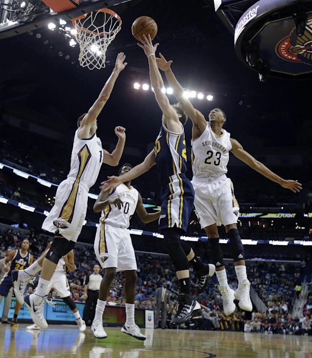 Utah Jazz shooting guard Gordon Hayward (20) goes to the basket between New Orleans Pelicans power forward Anthony Davis (23) and center Jason Smith, left, in the first half of an NBA basketball game in New Orleans, Wednesday, Nov. 20, 2013. (AP Photo/Gerald Herbert)